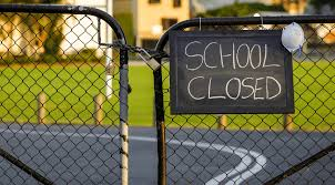 School Closed sign on a locked fence outside of a school